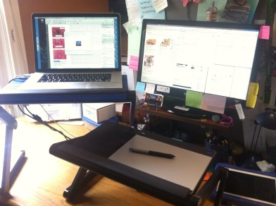 desk setup of dual screens and touch/stylus pad on standing desk arrangemetn